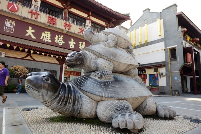Statue of three stacked turtles in a public square in front of a curios shop.